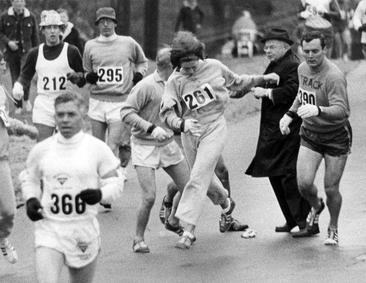 Sternstunde des Frauenlaufs: Kathrine Switzer mit der Nummer 261 aus Syracuse (N.Y.) kämpft sich am 21.04.1967 beim Boston Marathon an Marathon-Direktor Bill Cloney (im schwarzen Mantel) vorbei. Switzer setzte eine Revolution im Sport im Gang: Als erste Frau lief und beendete sie den Boston-Marathon.