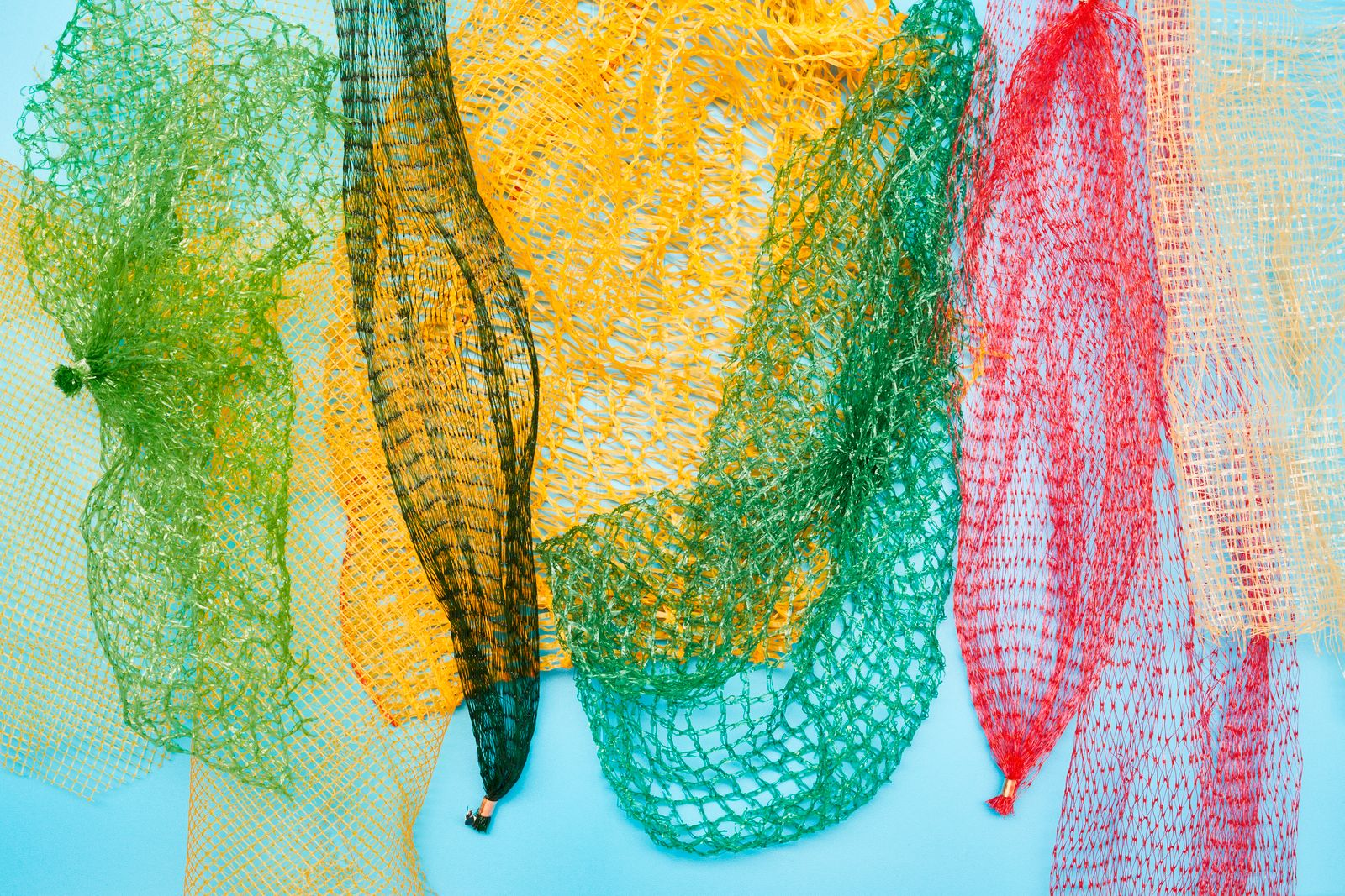 Colorful packaging nets on blue colored background, directly above shot of disposable plastic mesh