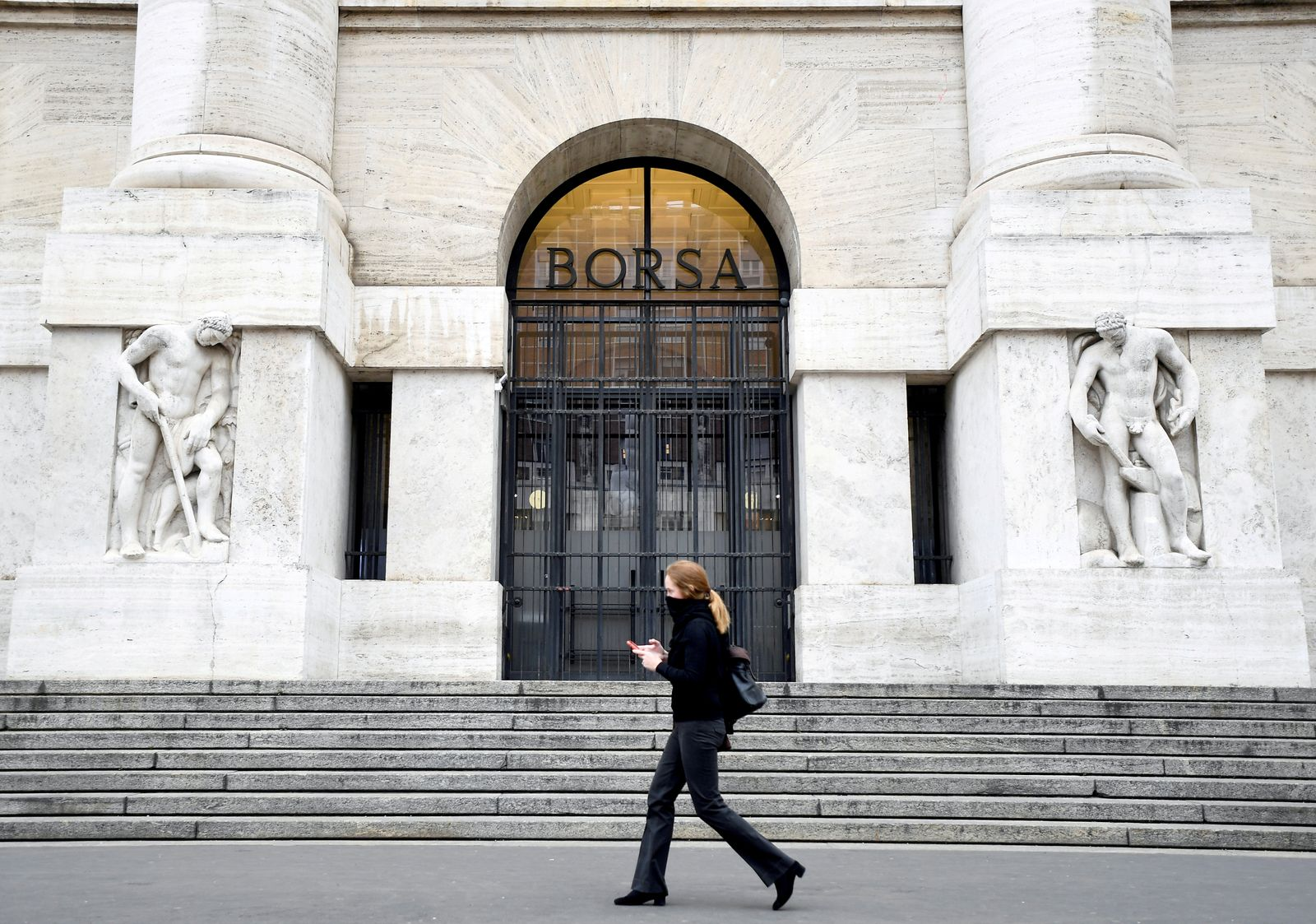 FILE PHOTO: A woman passes the Italian Stock Exchange in Milan