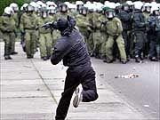 Gewaltausbruch: Ein vermummter Demonstrant schleudert einen Stein auf eine Polizeigruppe