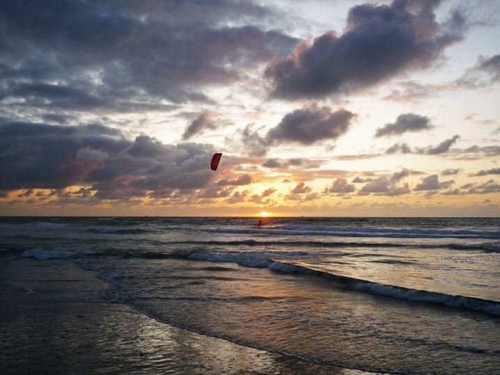 Nur ein einsamer Kitesurfer ist noch in denWellen: Sonnenuntergang auf Texel