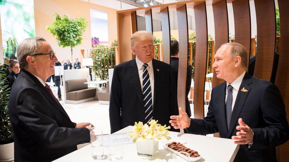 Das erste Treffen - und es dauerte gleich mehr als zwei Stunden: Russlands Präsident Wladimir Putin (r.) und US-Präsident Donald Trump (M.), dazu gesellt hat sich EU-Kommissionspräsident Jean-Claude Juncker (Foto vom Presseamt der Bundesregierung).