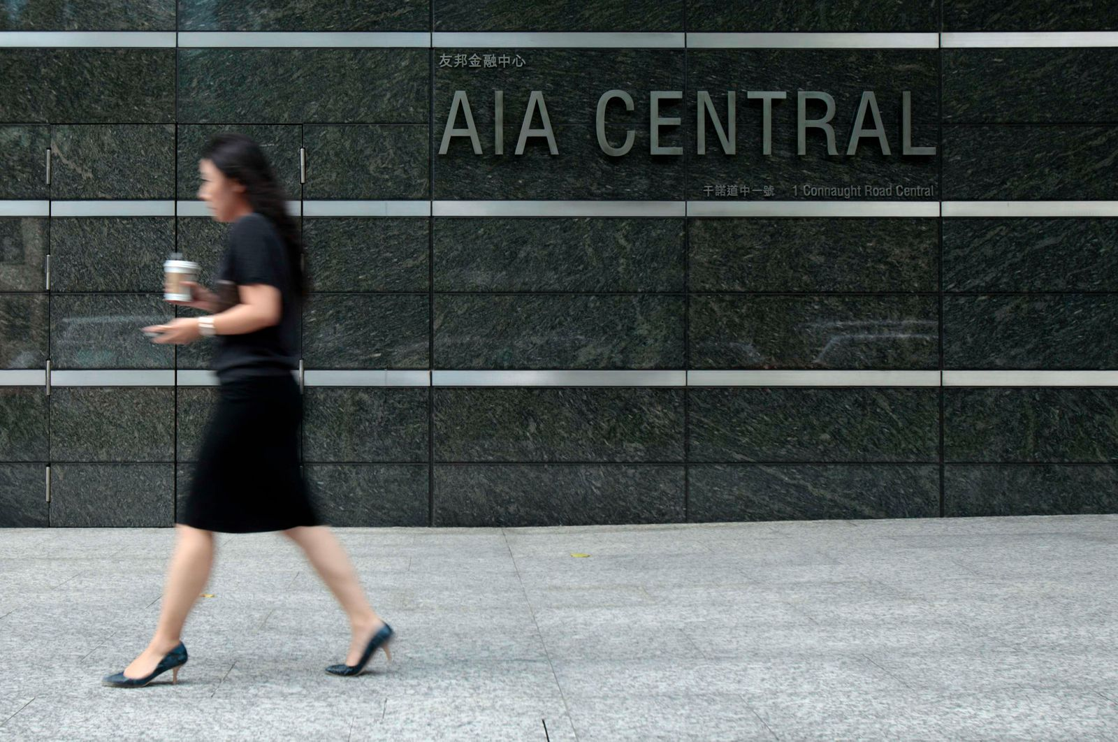 An office worker leaves the AIA tower in Hong Kong