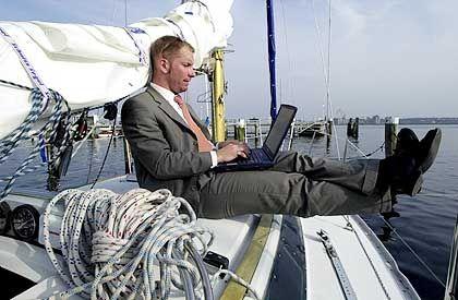 Überall online: Ein Mann arbeitet mit seinem Laptop auf dem Deck einer Segelyacht