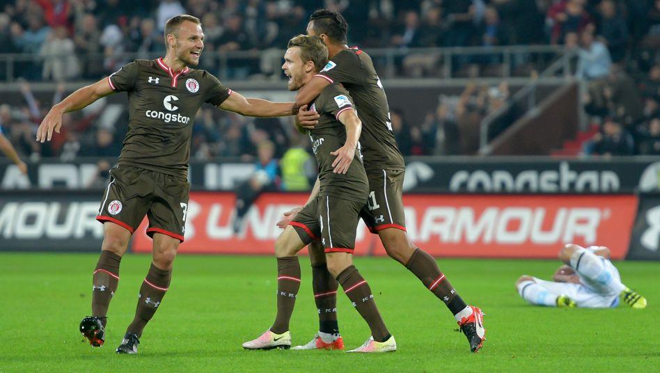 Jubel am Millerntor: FC St. Paulis Bernd Nehrig, Torschütze Christopher Buchtmann und Aziz Bouhaddouz (v.l.n.r.) feiern einen Treffer gegen den TSV 1860 München