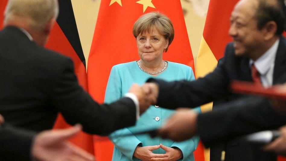 """Reicht euch die Hände: Merkel will einen Handelskrieg zwischen EU und China unbedingt vermeiden - und setzt sich dafür ein, China den Status einer """"Marktwirtschaft"""" zuzugestehen"""