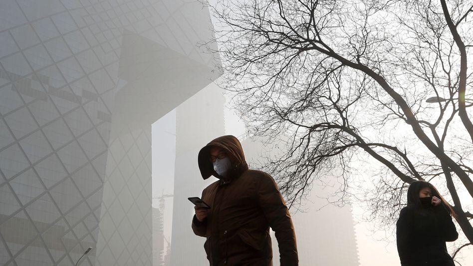 Menschen gehen durch den Smog in Peking