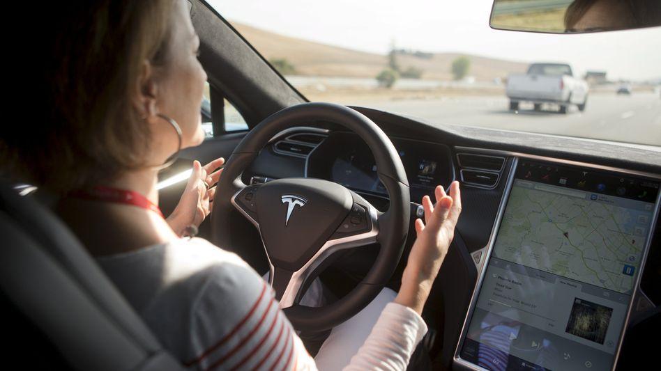 Nicht ungefährlich: Eine Frau lässt die Hände vom Steuer, während Teslas Autopilot-Assistenzsystem aktiviert ist (Archivbild von 2015)