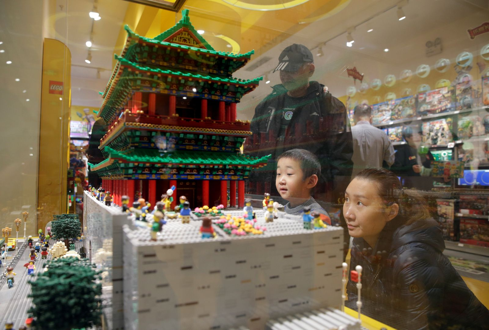 A boy and his mother look at the Zhengyang Gate Tower of Forbidden City made with Lego bricks at a Lego store in Beijing