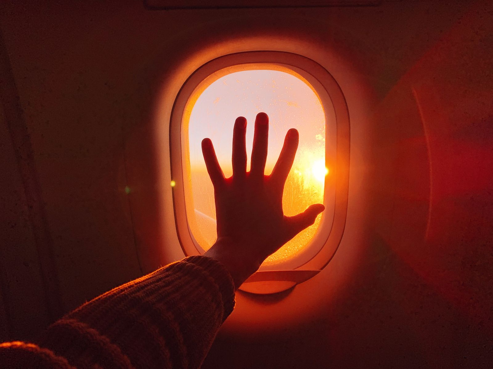 Touching plane window while flying in the sky during sunset