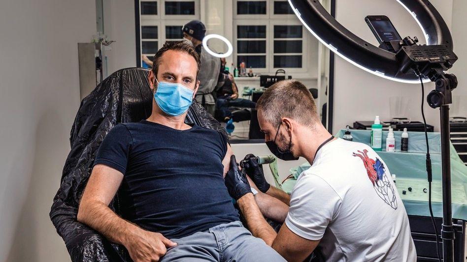 Voller Körpereinsatz:Edding-ChefPer Ledermannlässt sich im neuen Edding Tattoo Studio im Hamburger Chilehaus ein selbst designtes Tattoo stechen