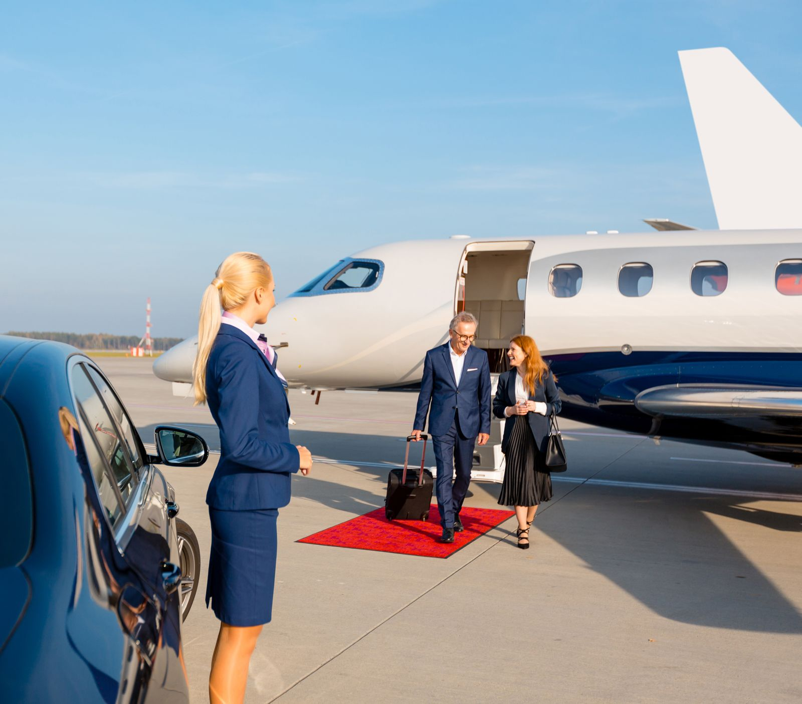 Mature professional couple in front of private jet at the airport
