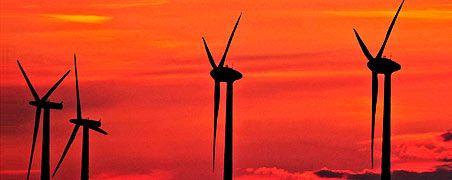 Schwarze Räder auf rotem Grund: In China boomt die Windkraftbranche so sehr, dass sie bereits das nationale Stromnetz überfordert