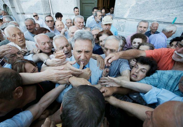 Eingekesselt: Ein Angestellter der National Bank von Griechenland (Mitte) verteilt Vorrang-Tickets an Rentner, die sich am eigens für sie geöffneten Bankschalter ihre Monatsrente oder zumindest Teile davon auszahlen lassen können