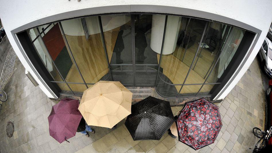 Stehen nicht im Regen: Nicht nur Manager der Hypo Real Estate, sondern auch die Spitzenkräfte anderer staatlich gestützter Banken verdienen wieder prächtig