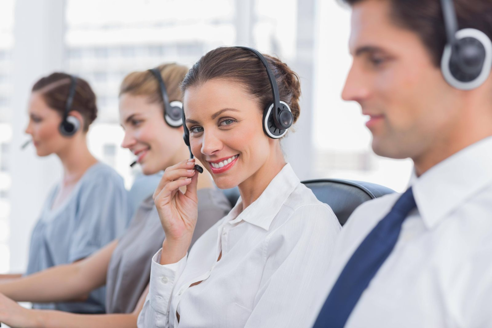 Attractive call centre agent with a headset with colleagues working around model released Symbolfoto