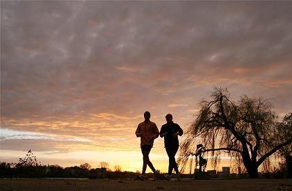 Unterwegs in klirrender Kälte: Zwei Jogger im winterlichen Sonnenaufgang