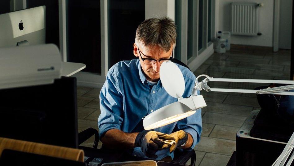 Kontrollfreak:Bei Blaken im Sauerland kontrolliert der Mann für die Qualitätssicherung nach jedem Arbeitsschritt die Einzelteile einer Uhr.