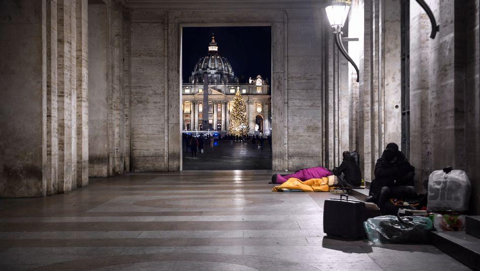 Ruhesuchende am Petersplatz: Die vatikanischen Museen sind seit Monaten geschlossen. Im Hintergrund Besucher, die die Weihnachtskrippe besichtigen.