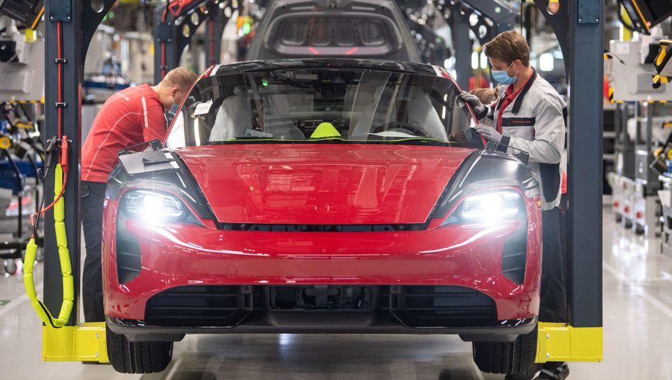 Porsche-Mitarbeiter mit dem Elektrohoffnungsträger Taycan