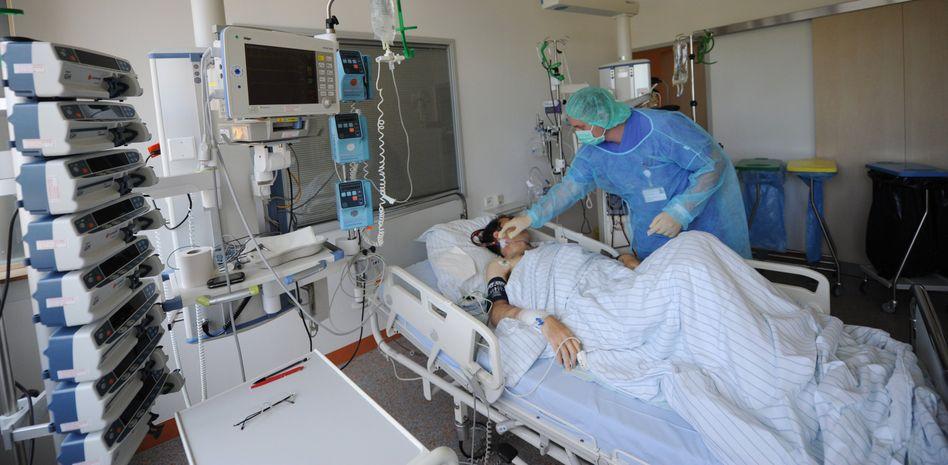 Krankenpfleger mit einem mit dem Ehec-Erreger erkrankten Patienten: Die Welle der von Ehec ausgelösten gefährlichen Durchfallerkrankungen ist noch nicht vorüber