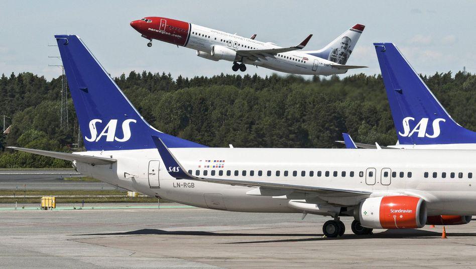 Zwei Beispiele von vielen in der Corona-Krise: Die skandinavische Airline SAS und die Billigfluglinie Norwegian Air (rot-weißes Flugzeug, Bild Archiv) ringen ums Überleben.