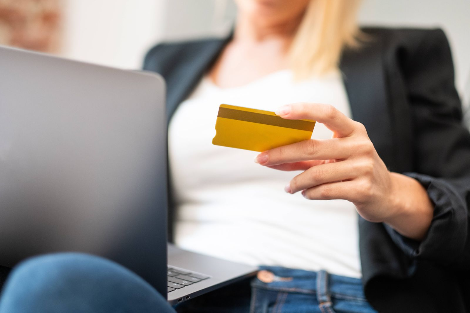 Cropped unrecognizable blonde female in casual clothes entering credit card credentials on laptop while sitting in comf