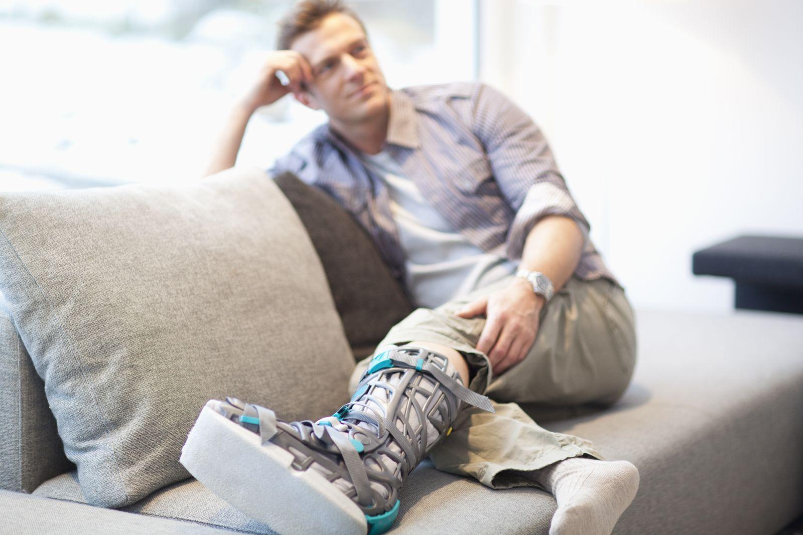NICHT MEHR VERWENDEN! - Mann auf Sofa mit Gips / Gipsbein / Beinbruch