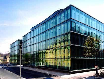 Geschuppte Scheiben: Die Doppelglasfassade der neuen Münchener-Rück-Zentrale, in dem sich das alte Hauptgebäude spiegelt, strahlt Innovation aus. Der glasdominierte Bau stammt im Kern aus dem Jahr 1970 und wurde im Jahr 2002 nach Plänen des Architektenbüros Baumschlager und Eberle runderneuert.