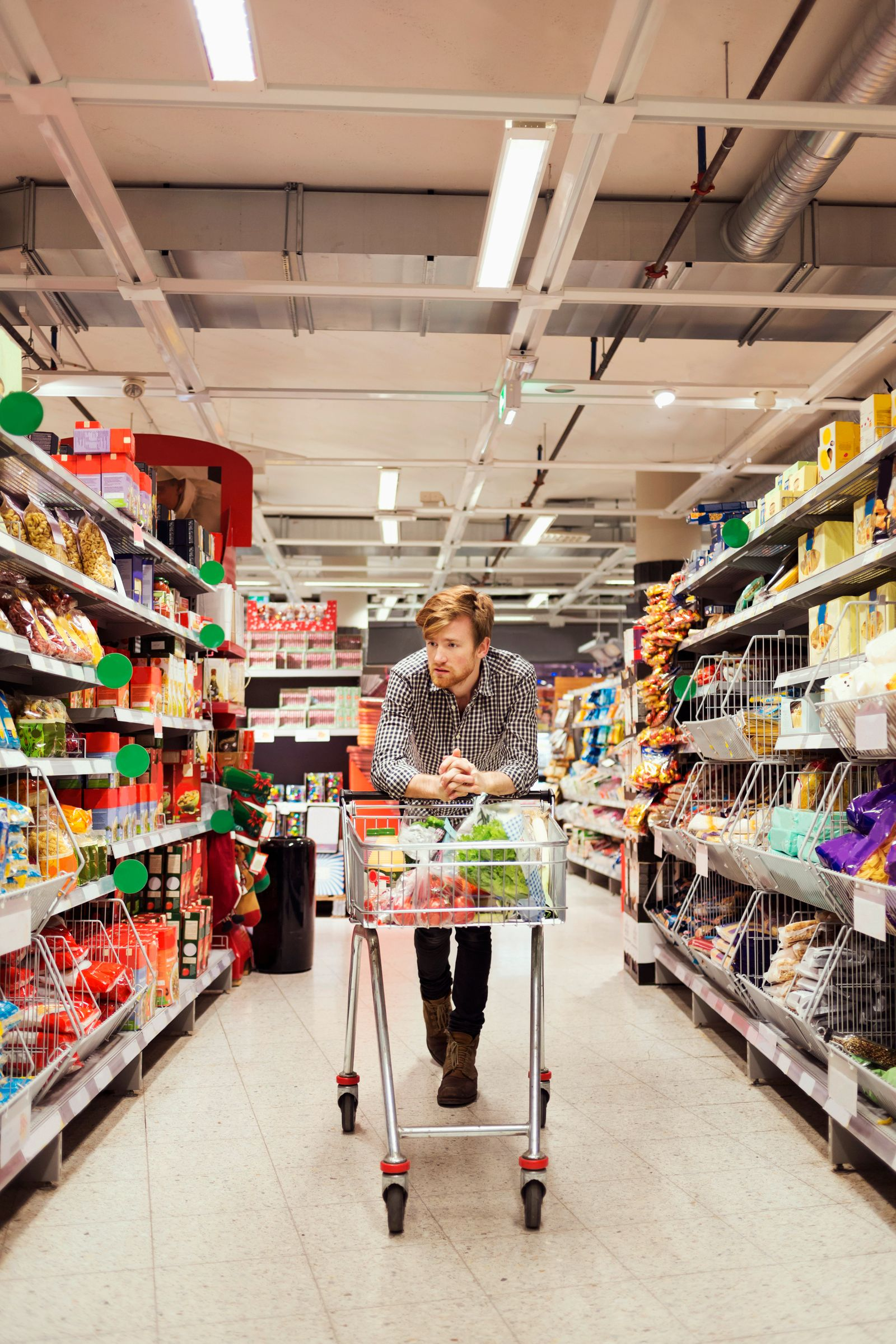 Young man leaning on shopping cart at supermarket aisle