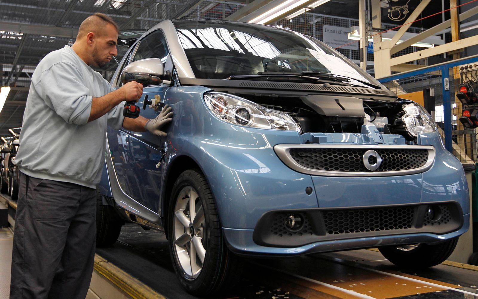 An employee at the Smart Cars factory works on the Smart Fortwo assembly line in Hambach