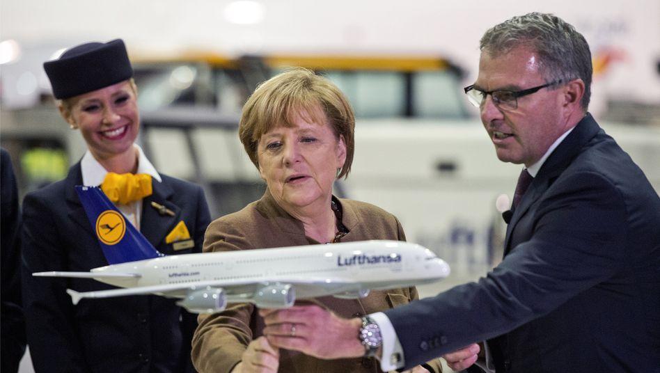 Rüttelflug der Lufthansa: Chefpilot Spohr (rechts) und Kanzlerin Merkel (Mitte) bemühen sich um Stabilität