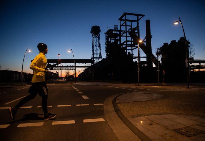 Ja, eine blaue Stunde gibt es auch im schwarzgelben Dortmund: ein Läufer vor dem ehemaligen Hüttenwerk Phoenix-West