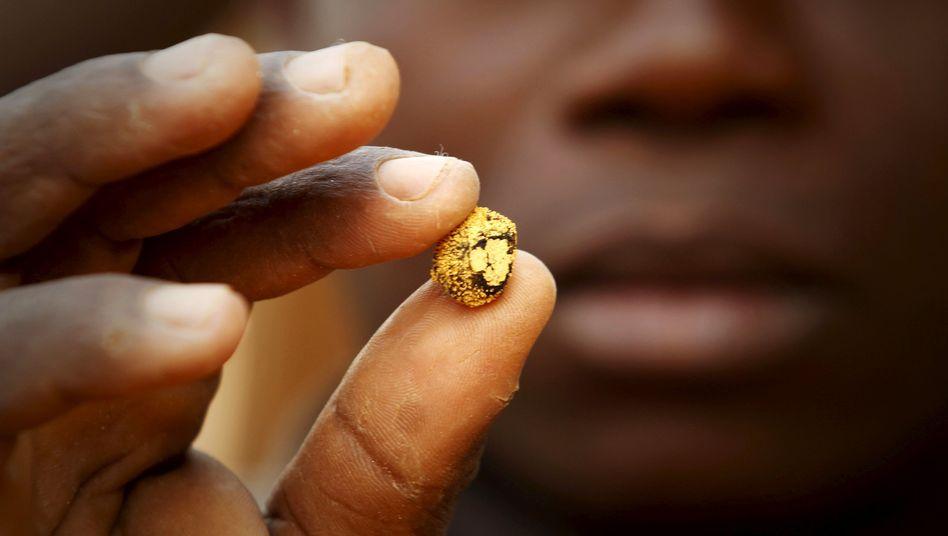 Minenarbeiter mit Goldklumpen: In der Branche der Goldproduzenten gibt es bereits den zweiten großen M&A-Deal binnen kurzer Zeit.