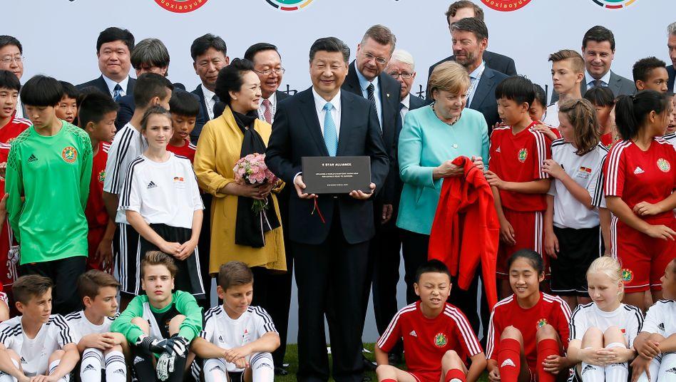 Fußball verbindet: Chinas Staatspräsident Xi Jinping, Bundeskanzlerin Angela Merkel und der deutsch-chinesische Fußball-Nachwuchs - in Adidas-Trikots. Adidas-Chef Kasper Rorsted (genau hinter Merkel) dürfte das Bild wohl jetzt über seinem Schreibtisch aufhängen