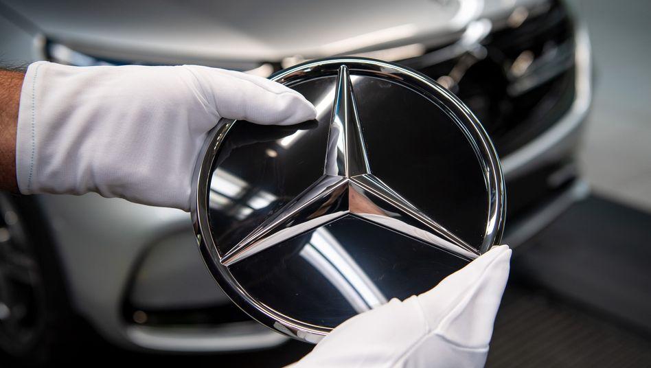 Mercedes-Werk Bremen: Ein Mitarbeiter montiert den Stern am Kühlergrill