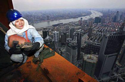 Große soziale Kluft: Bauarbeiter über der Skyline von Shanghai