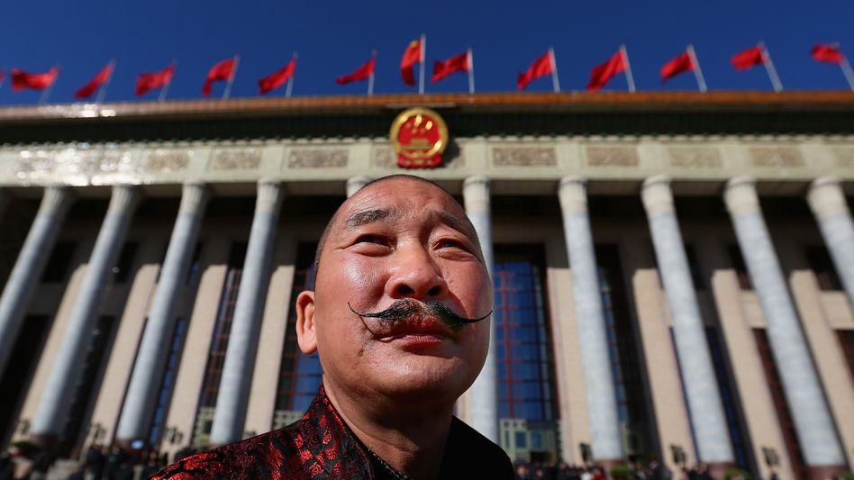 """Ein Delegierter vor der """"Halle des Volkes"""" in Peking: Beim nationalen Volkskongress gibt die Führung ein bescheideneres Wachstumsziel von 6,5 Prozent pro Jahr aus"""