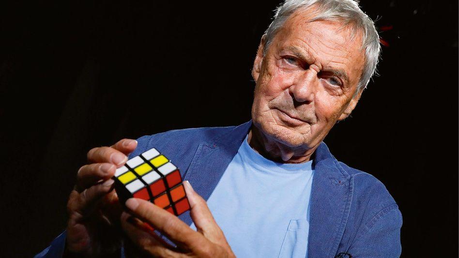 Ernő Rubik mit seiner Entdeckung: Dem bunten Zauberwürfel.