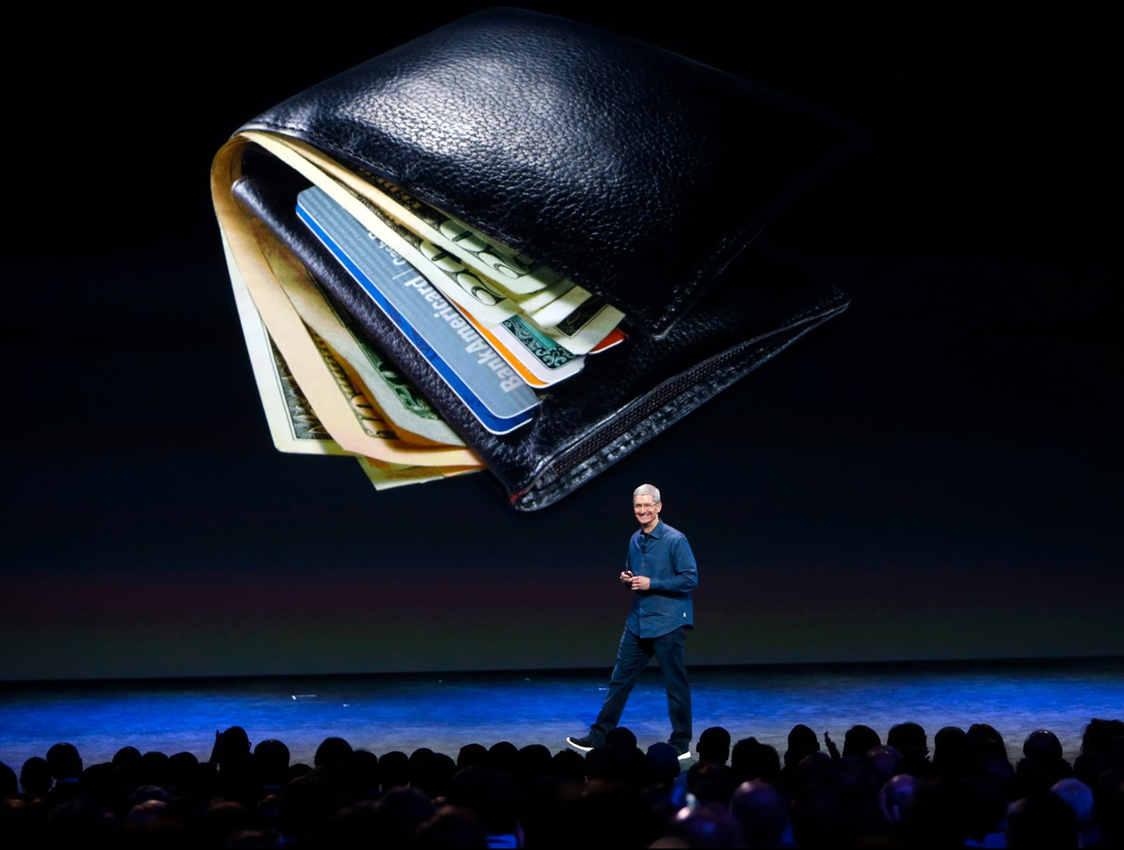 Apple CEO Tim Cook, standing in front of an image of bulging wallet, begins to describe a new way to pay, while introducing the iPhone 6 and the Apple Watch at the Flint Center in Cupertino, Calif., on Tuesday, Sept. 9, 2014. (Karl Mondon/Bay Area News