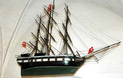 """Erinnerungsstück: An einem starken Seil hängt das historische, hölzerne zwei Meter lange Schiffsmodell """"Tordenskjold"""" in der Flensburger Heiliggeistkirche. Die Kriegsfregatte schmückt das dänische Gotteshaus mitten in der Altstadt"""