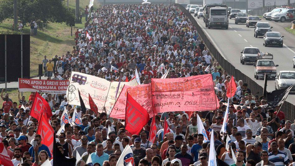 Straßenblockade: Tausende aufgebrauchte Arbeiter von Mercedes-Benz und Volkswagen demonstrierten am Montag nahe Sao Paulo gegen Enlassungen der Konzerne