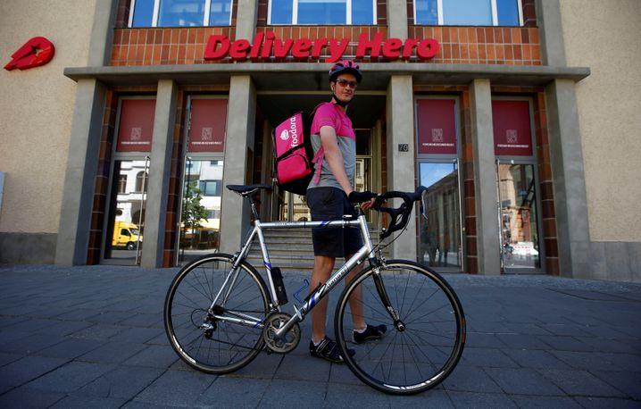 Ein Foodora-Fahrer steht vor der Zentrale von Delivery Hero in Berlin