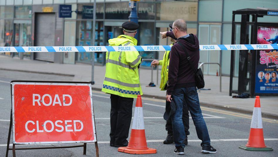 Polizisten an der Absperrung der Straße, die zur Manchester Arena führt. Dort hat eine Explosion am Abend mindestens 22 Menschen getötet