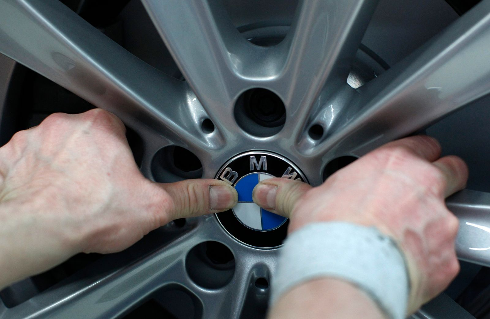 Employee places company logo on BMW wheel rim at production line of German car manufacturer's plant in Dingolfing