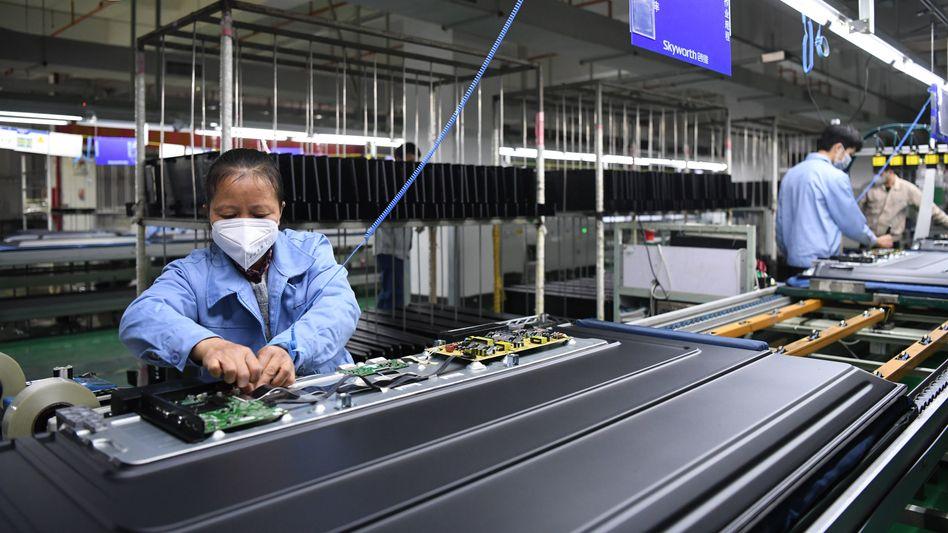 China, Guangzhou: Angestellte arbeiten mit Mundschutz