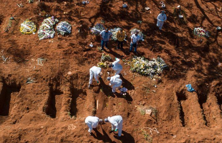 beisetzung im Akkord: Angestellte in Schutzkleidung in Sao Paulo beerdigen ein weiteres Covid-19-Opfer.