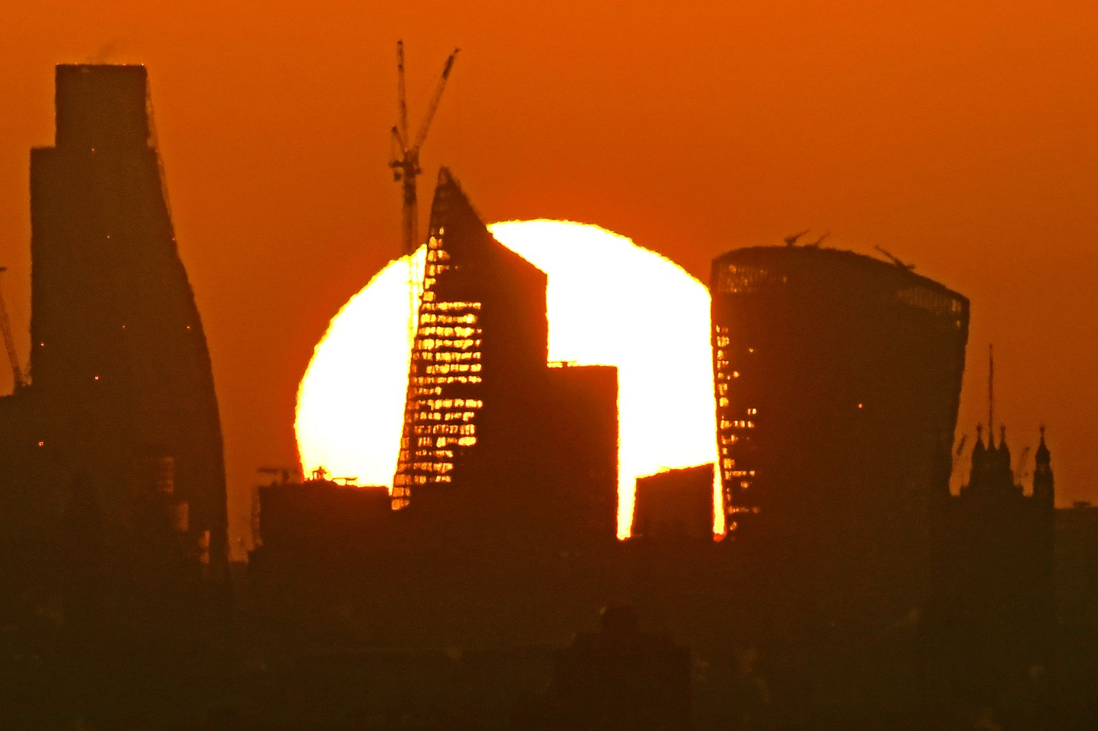 The sun is seen rising over skyscrapers in the City of London financial district in London
