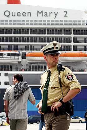 """Ein Polizist am Eingang zur """"QM 2"""": Rund 200 Sicherheitskräfte sichern den Luxusliner"""