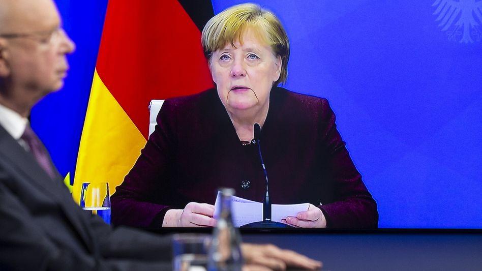 Agenda gesetzt: Klaus Schwab, Chef des Weltwirtschaftsforums, vor einem Videoschirm mit Angela Merkel